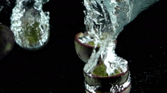 FivePassion Fruits Splashed into Water in Slow Motion - stock footage