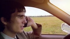 Stock Video Footage of Young handsome dark-haired man driving car in the field and speaking on mobile