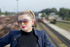 the woman's portrait in sunglasses against railway tracks - stock photo