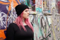 Stock Photo of woman with pink hair piercings and tattoos leaning against graffiti wall