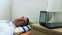 Young man sleeps in bed - smartphone and tablet on bedside table Stock Footage