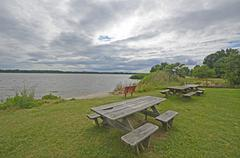 Picnic tables on the waters edge Stock Photos