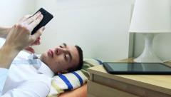 Young man lying in bed and works on smartphone - tablet on bedside table Stock Footage