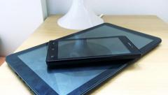 Tablet and smartphone on bedside table next to the bed in bedroom  Stock Footage