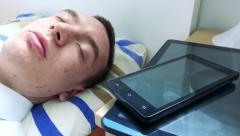 Young man sleeps in bed - smartphone and tablet on bedside table - closeup Stock Footage
