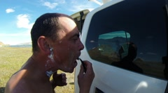 Stock Video Footage of Man Shaves Looking at His Reflection in Glass of the Car in Mongolian Highland