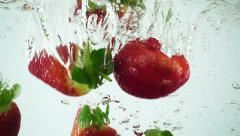 Stock Video Footage of Ultra Slowmo Multiple Strawberries Splashed into Water on White Background