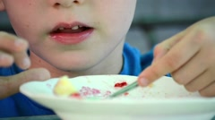Early age boy sitting at the table and eat with a spoon from a deep dish Stock Footage