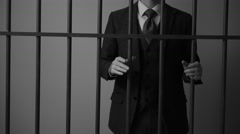 A white collar ponze scheme criminal grips bars in prison - stock footage