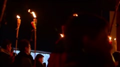 Column of children marching on a street with lit torches to commemorate - stock footage