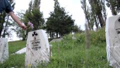 Man placed a bouquet of flowers on a grave cross of unknown soldier - stock footage