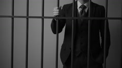 A wealthy criminal grips bars in prison cell Stock Footage