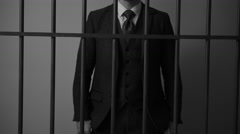 A white collar criminal stands behind bars in jail - stock footage