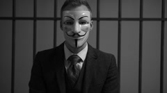 Anonymous hacker man sighes in prison (B/W Version) - stock footage