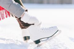 Girl in dress skates mittens tying shoelaces Stock Photos