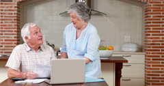 Stock Video Footage of Senior couple paying their bills with computer