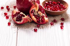 Some red juicy pomegranate, whole and broken, on rustic wooden table - stock photo