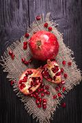 Some red juicy pomegranate, whole and broken, on rustic wooden table Stock Photos