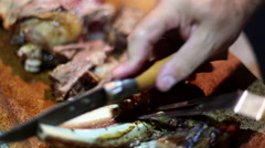 Man cutting roasted meat on a cork tray with a sharp knife in Sardinia, Italy. - stock footage