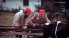 1946: Family in red hats petting cow at rural farmstead. - stock footage