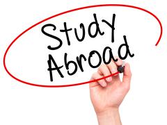 Man Hand writing Study Abroad with black marker on visual screen - stock photo