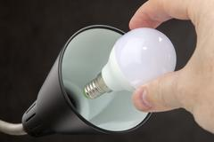 Installing LED lamp with lampshade Household lamps, black background. - stock photo