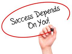 Man Hand writing Success Depends On You! with black marker on visual screen Stock Photos