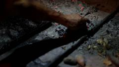 Man picking up some potatoes from the ash in a fireplace. Stock Footage