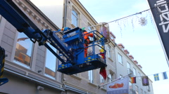 Man in an arial work platform are pulling down som flags Stock Footage