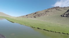 Stock Video Footage of the River Flowing at a Rocky Hill in Mongolian Highland
