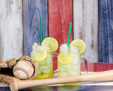 Jar glasses filled with cold lemonade with baseball sporting items.  Faded wo Stock Photos