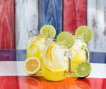 Front view of a glasses filled with cold lemonade.  Faded wooden boards paint - stock photo