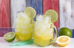 Close up of a glasses filled with cold lemonade.  Faded wooden boards painted - stock photo