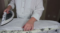Woman ironing a white shirt with a steam iron on a ironing board Stock Footage