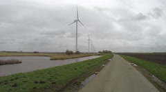 Wind turbines lined up moving on road first person view polder landscape 4k - stock footage
