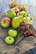 Apples, pears and grapes placed on the rustic style wooden table. - stock photo