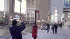 Asian man taking picture of tourist woman in winter in Times Square - snowing Stock Footage