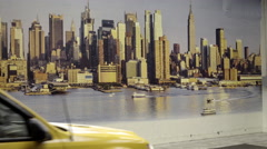 Taxi cab caravan passing by photograph of Manhattan skyline Times Square NYC Stock Footage