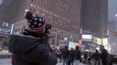 Tourist with hat and coat taking photo in Times Square snowing in winter 4K NYC Stock Footage