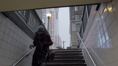 Man carrying coffee into subway, downstairs, snowing in cold winter in 4K, NYC Stock Footage