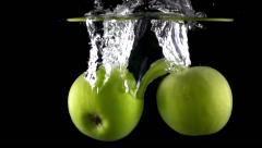 Two green apples fall down in water against black background, super slow motion Stock Footage