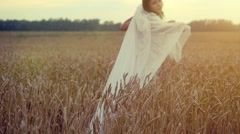 Woman walking in a wheat field. Hand of a young girl touching corn ears in field Stock Footage