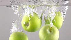 Close up shot: green apples fall in water, gray background, super slow motion - stock footage