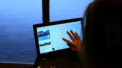 Girl tourist near sea window sitting with laptop planning his travel journey Stock Footage