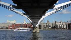 Passenger boats passes below the Millennium Bridge on the Thames Stock Footage