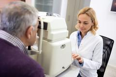 Stock Photo of Female eye specialists determines diopter using apparatus