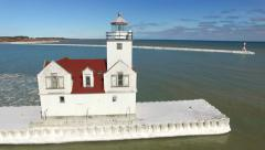 Winter flyby of scenic white lighthouse on ice-glazed pier Stock Footage