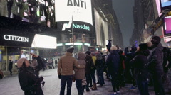 tourists on camera looking at Revlon ad screen - snowing Times Square night NYC - stock footage