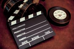 Movie clapper board and filmstrip selective focus Stock Photos