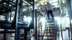 Worker climb metal stairs at modern food factory. Interior of milk factory Stock Footage